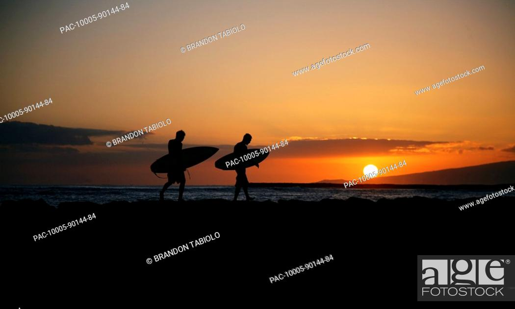 Stock Photo: Hawaii, Oahu, Waikiki, Two Surfers walking along the shoreline as the beautiful sunsets.