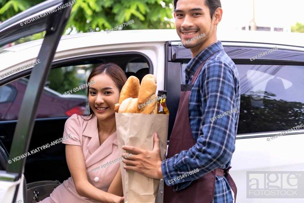 Stock Photo: Delivery staff giving grocery bag set to asian customer woman at drive thru service station of Supermarket. Drive thru is popular service and new normal after.
