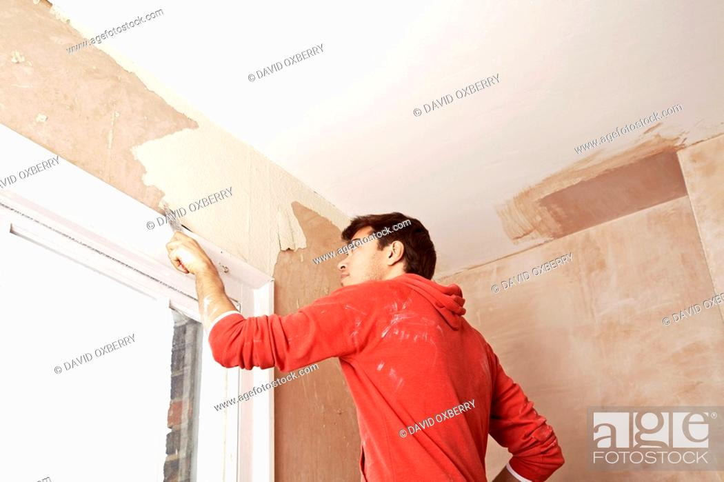 Stock Photo: Man scraping paint off wall in unrenovated room low angle view.