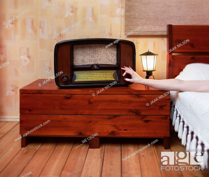 Stock Photo: Woman`s hand turning radio on or off. Old classical retro radio and lamp on bedside tabel.