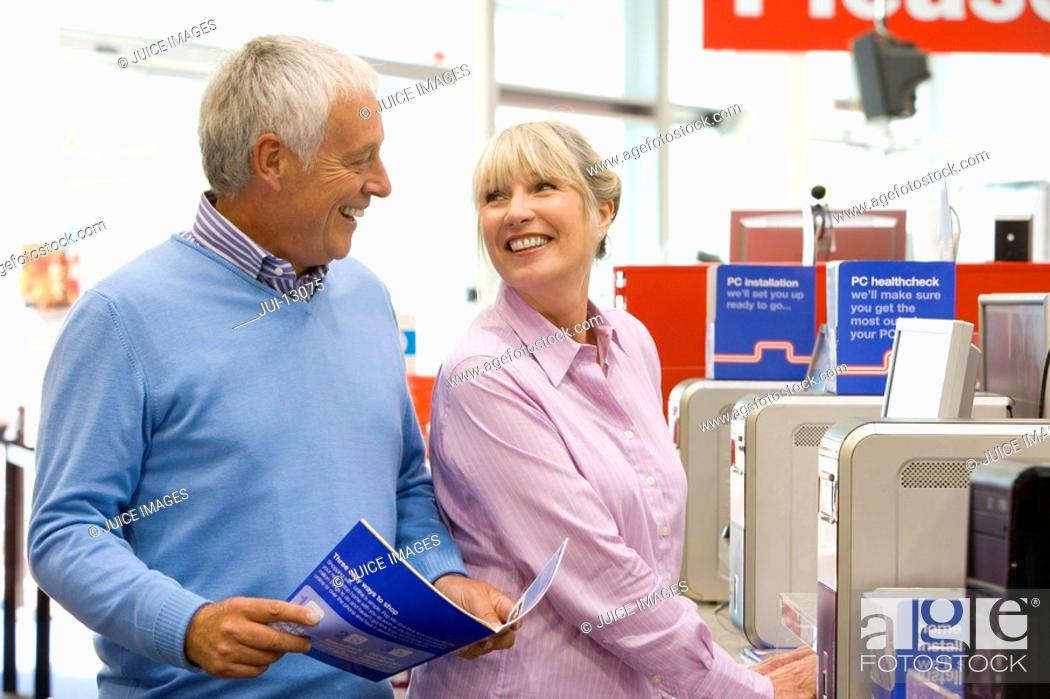 Stock Photo: Mature couple shopping for computer, smiling at each other.