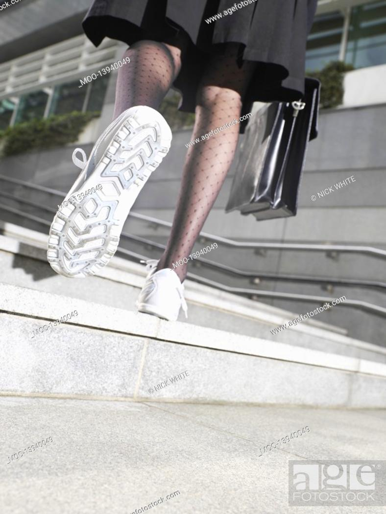 Stock Photo: Business woman wearing running shoes walking up steps low section low angle view back view.