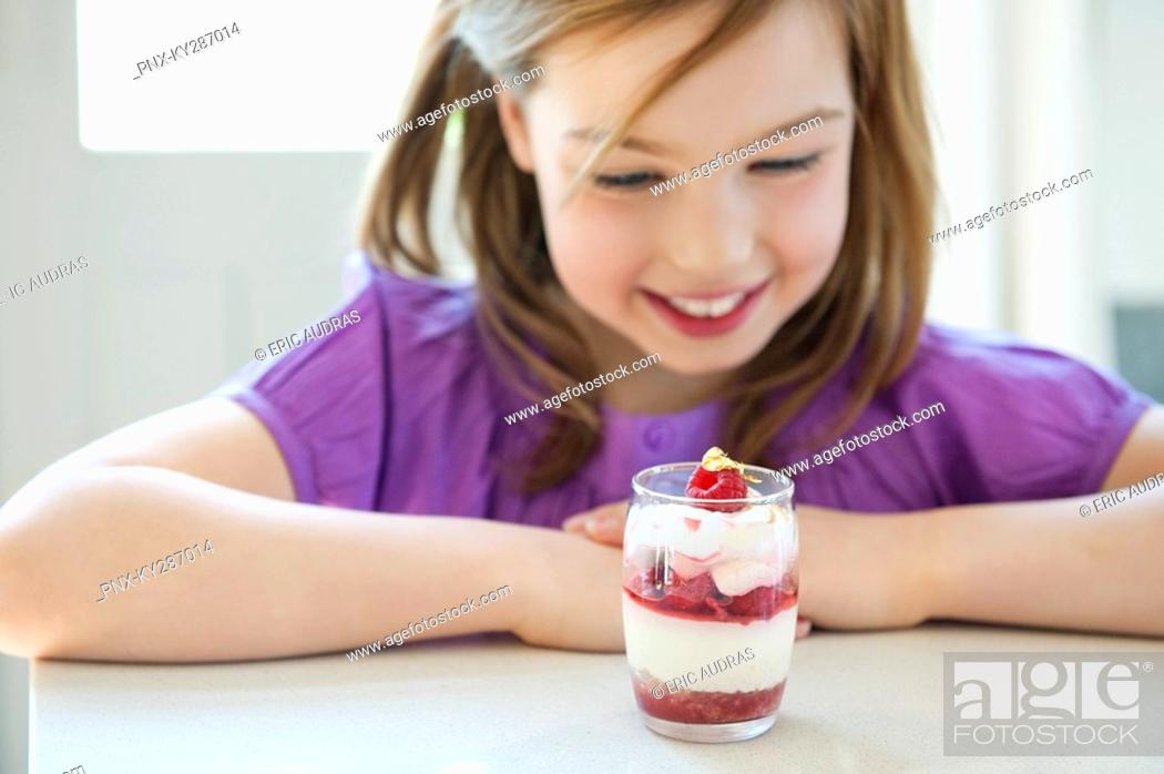 Stock Photo: Girl looking at a glass of ice cream.