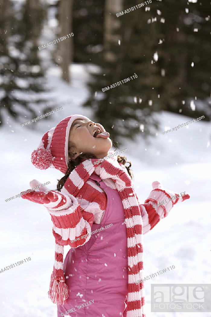 Stock Photo: Girl catching snowflakes with tongue.