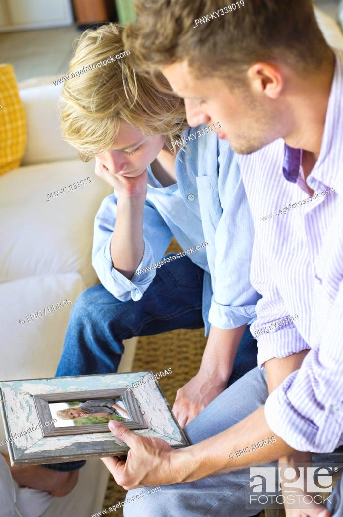 Stock Photo: Man and a little boy looking at picture frame.