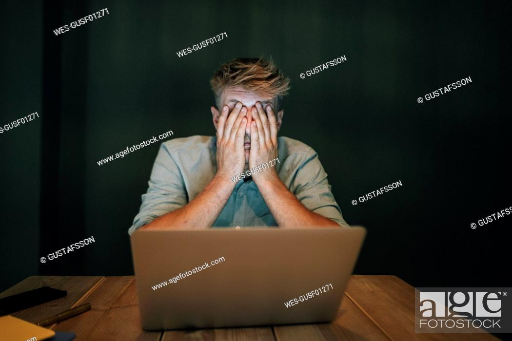 Stock Photo: Tired man sitting in office, working late in his start-up company, covering eyes.