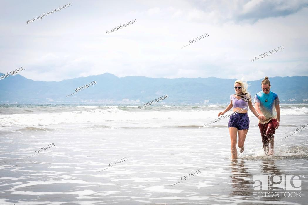 Stock Photo: Beach scene with young woman and man running, Riviera Nayarit, Pacific Coast, Mexico.