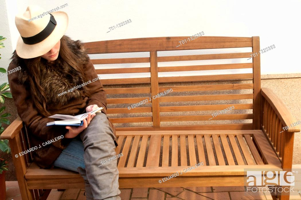 Stock Photo: Fashionable girl with Panama hat reading a book outdoors.