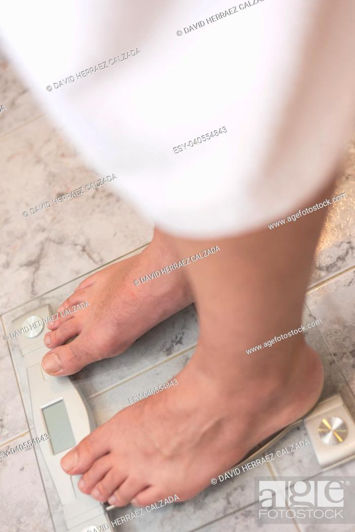 Stock Photo: Man feet standing on weight scale.