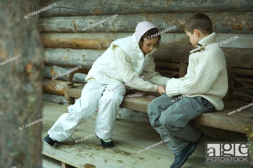 Stock Photo: Girl and boy playing cards outdoors, dressed in winter clothing.