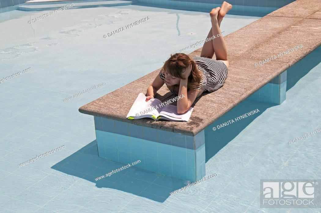 Stock Photo: Young female studying at poolside.
