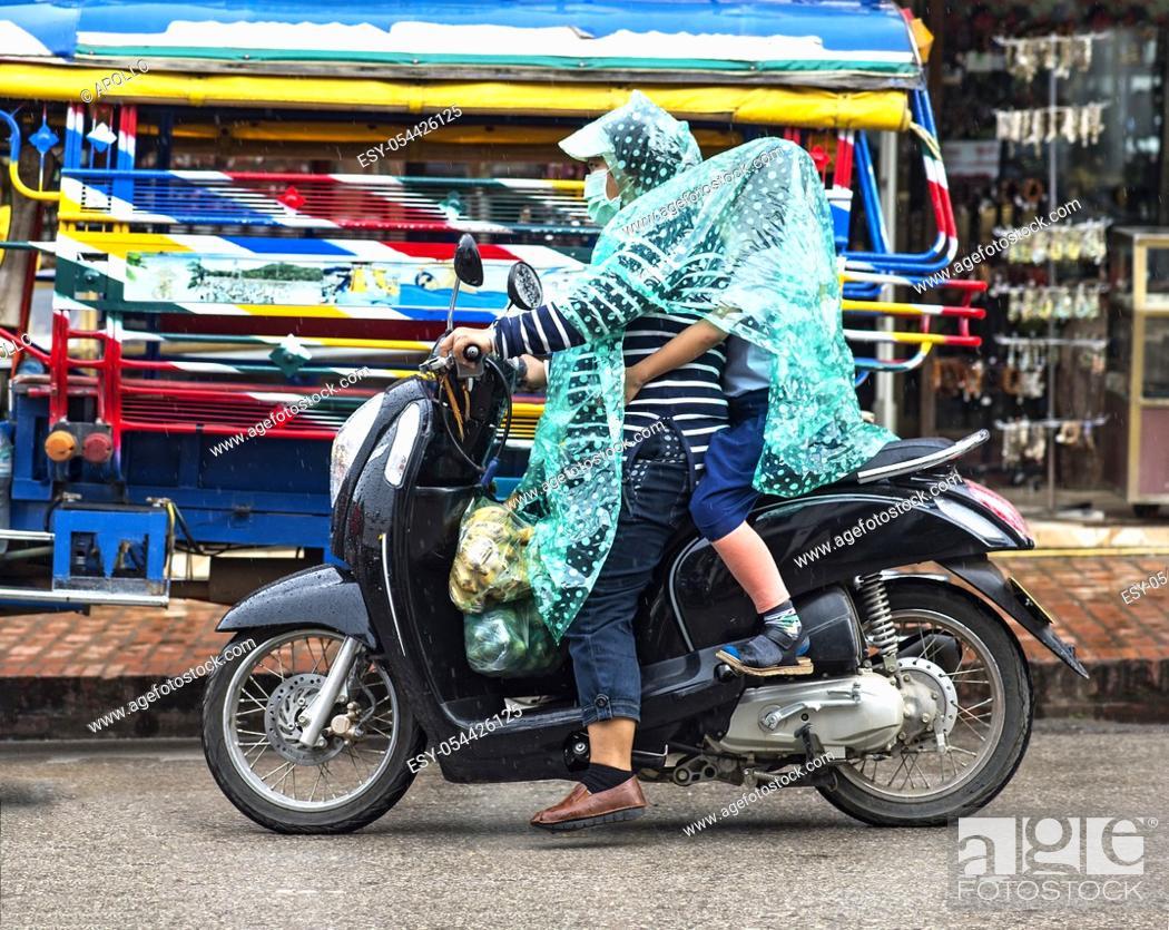 Photo de stock: Riding in the rain, Luang Prabang, Laos.