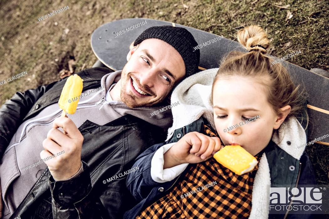 Stock Photo: Father and daughter resting on skateboard, eating ice cream.