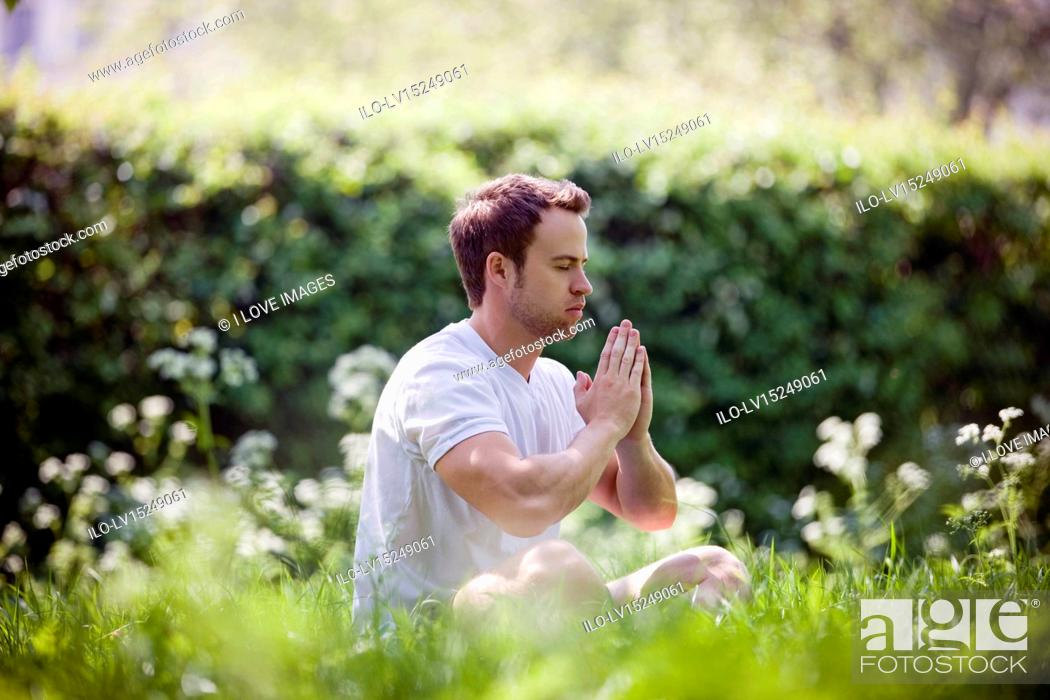 Stock Photo: A young man meditating outdoors.