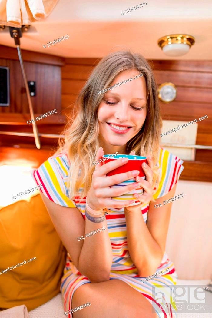 Stock Photo: Young woman enjoying coffee in sailboat cabin.