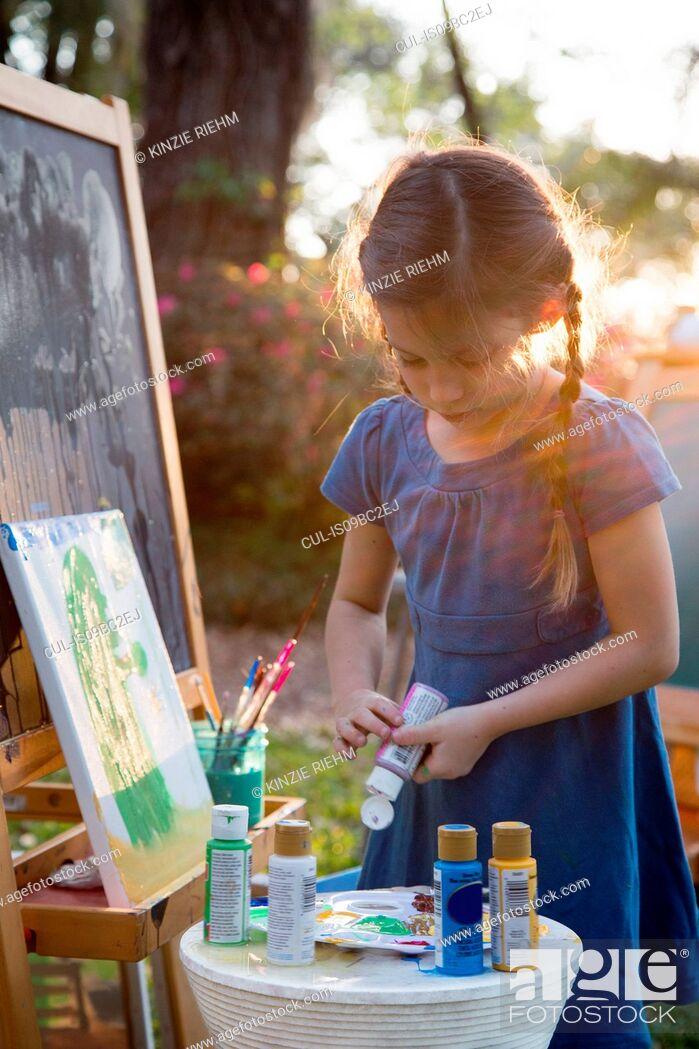 Imagen: Girl squeezing paint onto palette in garden.