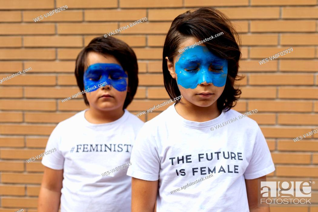 Stock Photo: Portrait of two brothers with painted blue masks on their faces wearing t-shirts with feministic imprints.