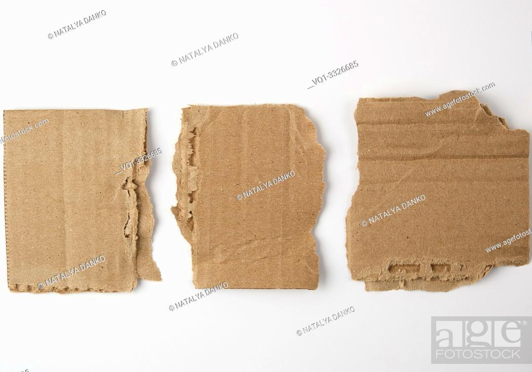 Stock Photo: three pieces of torn brown paper on a white background, close up.