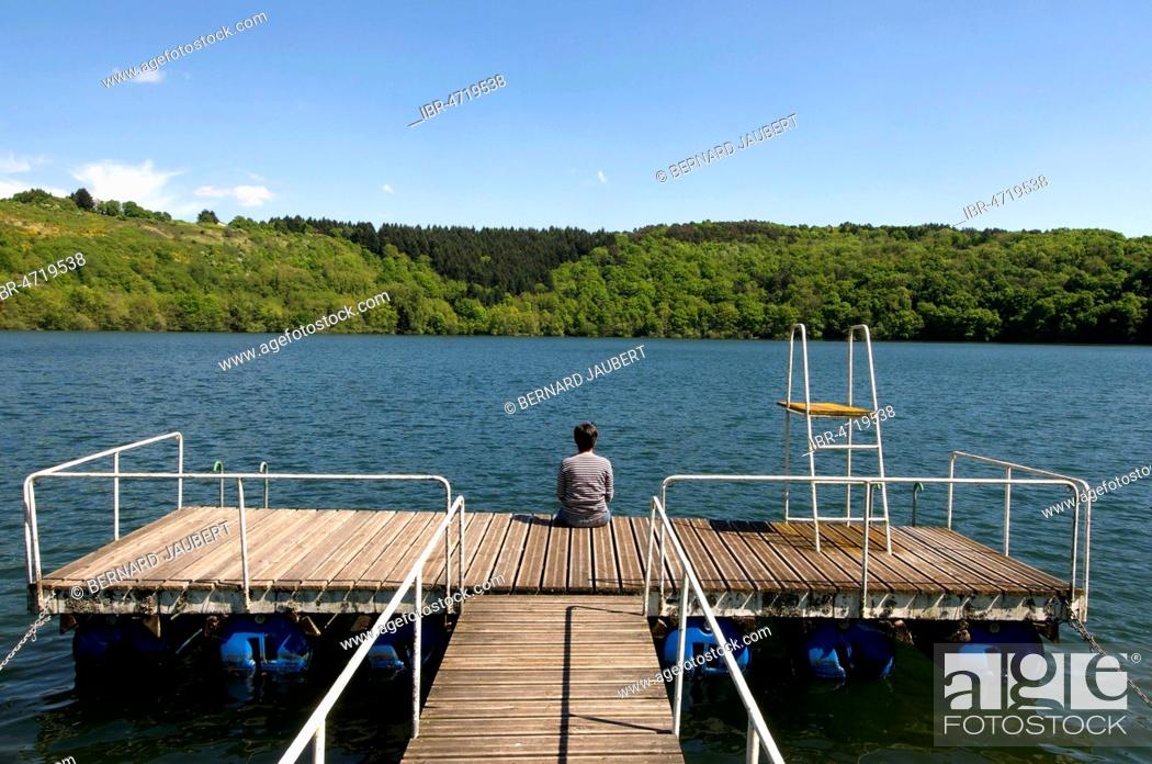 Stock Photo: Adult woman back sitting on a pontoon at the edge of a lake surrounded by rows of trees, Puy de Dome department, Auvergne, France.