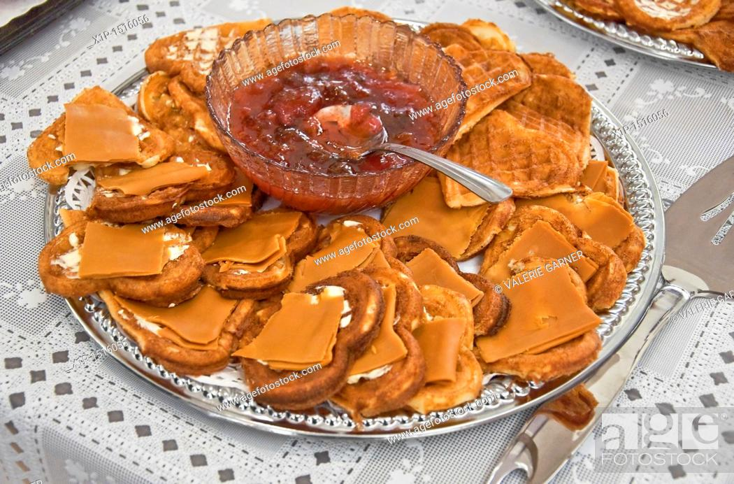 Stock Photo: This traditional Norwegian food, is a silver platter of heart shaped waffles with slices of brown goat cheese on top  In the center of the platter is a crystal.