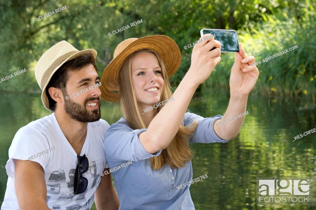 Stock Photo: Smiling young couple at a lake taking a selfie.