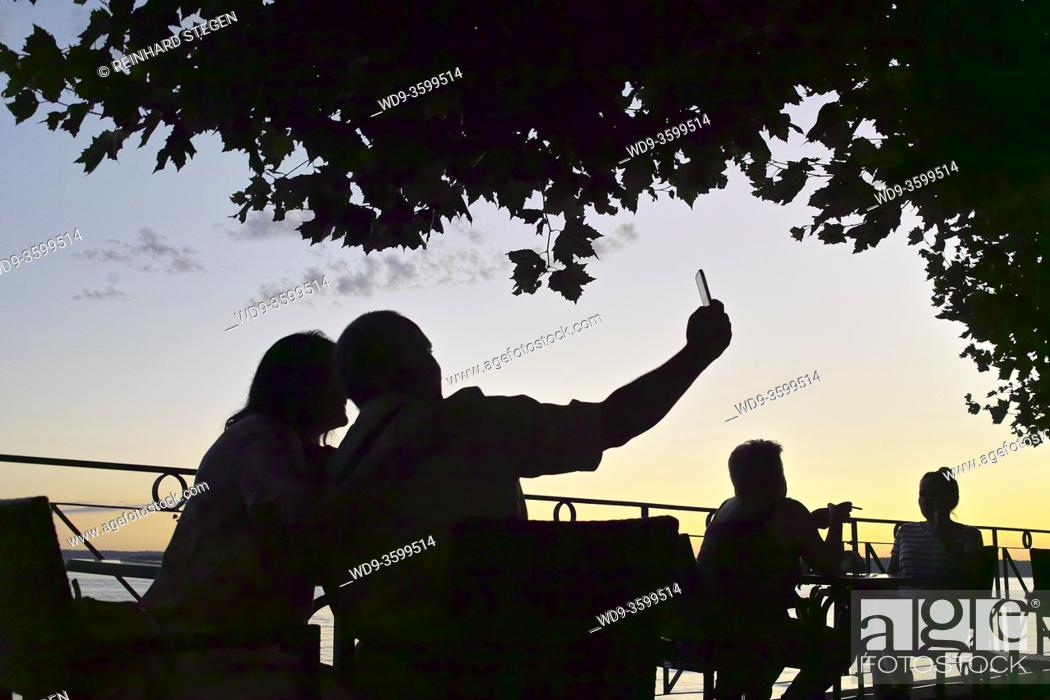 Stock Photo: couple taking selfie by lake at sunset.