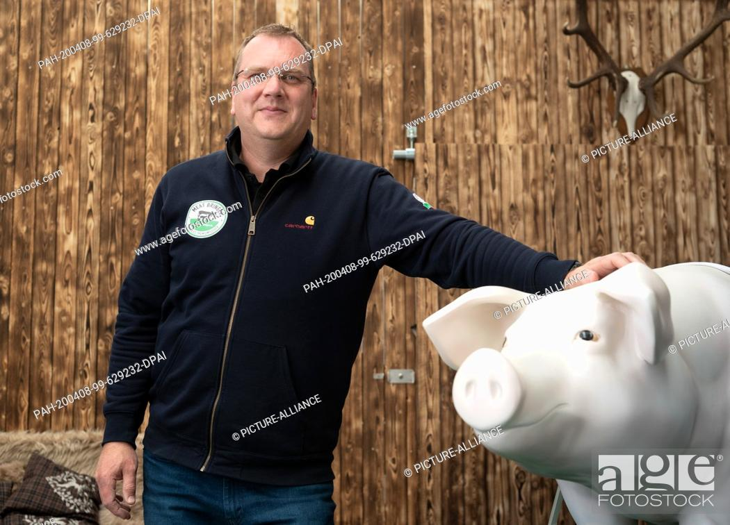 """Stock Photo: 06 April 2020, Brandenburg, Wildau: Olaf Mahr, founder and operator of """"""""Meat Bringer"""""""", stands behind a life-size pig made of plastic in one of his business."""