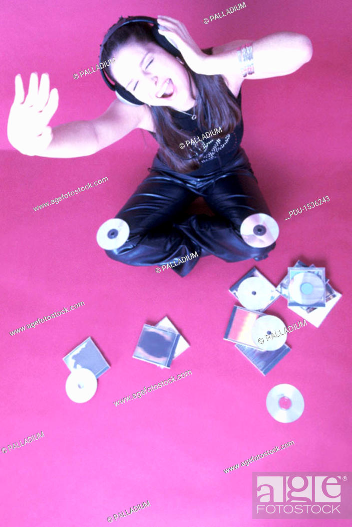 Stock Photo: Elevated view of a teenage girl (17-20) sitting on the floor dancing wearing headphones (toned).