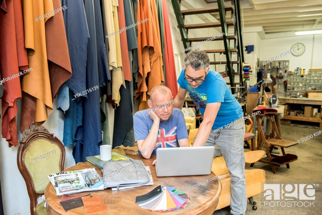 Stock Photo: Tilburg, Netherlands. Josef and Werner are apprentice upholsterer and his male partner, both looking at an Apple's notebook, viewing their newly made images.