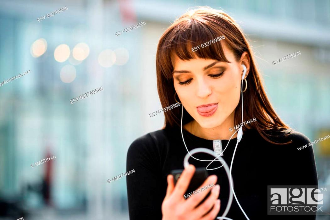 Stock Photo: Young woman sticking out tongue while making video call in street.