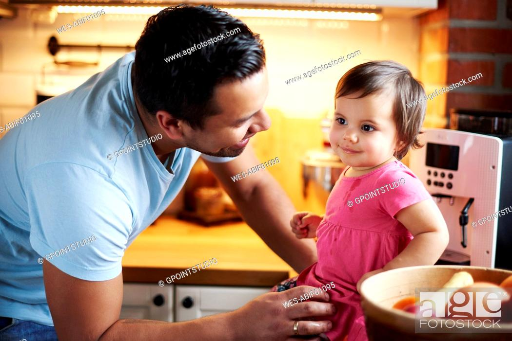 Stock Photo: Smiling father looking at baby girl sitting on counter in kitchen at home.