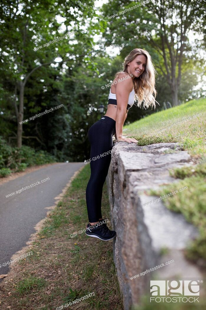 Imagen: Smiling Young Adult Woman in Fitness Attire Holding Herself up on Stone Wall.