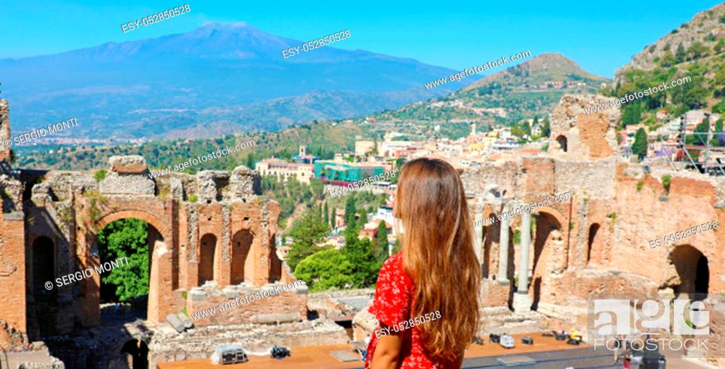 Stock Photo: Beautiful young female model in the ruins of the ancient Greek theater in Taormina with the Etna volcano on the background, Sicily, Italy.