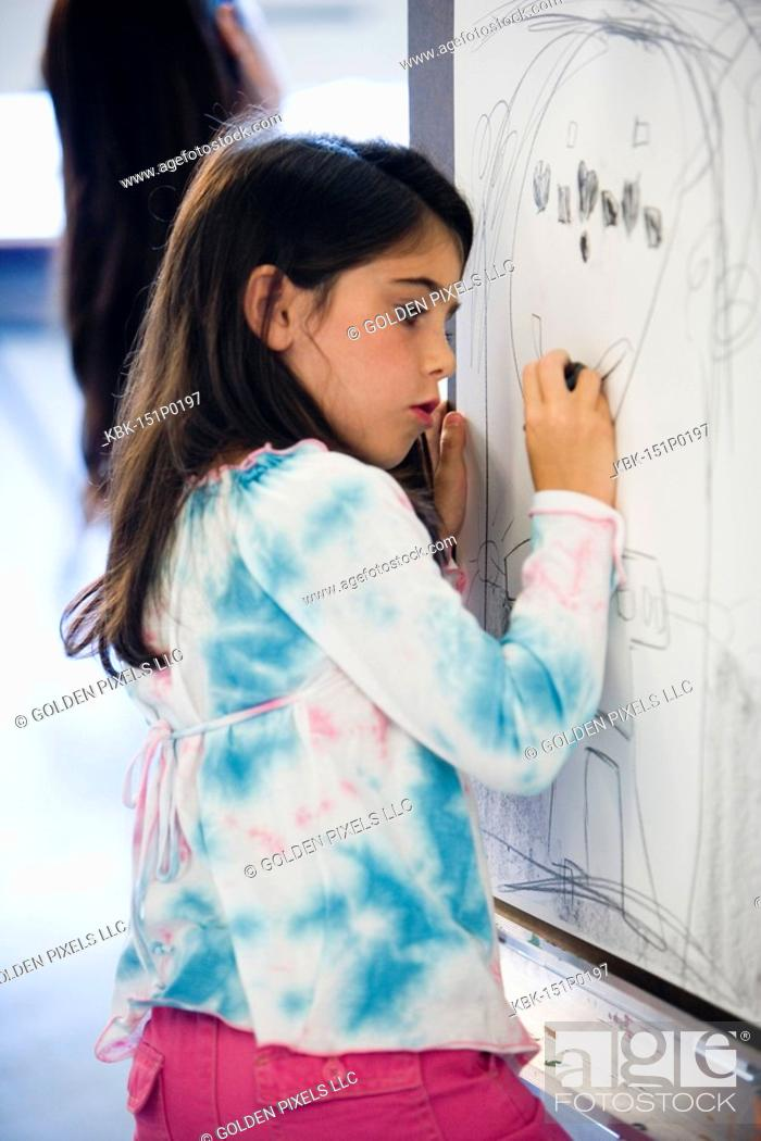 Imagen: Girl drawing on easel in art class.