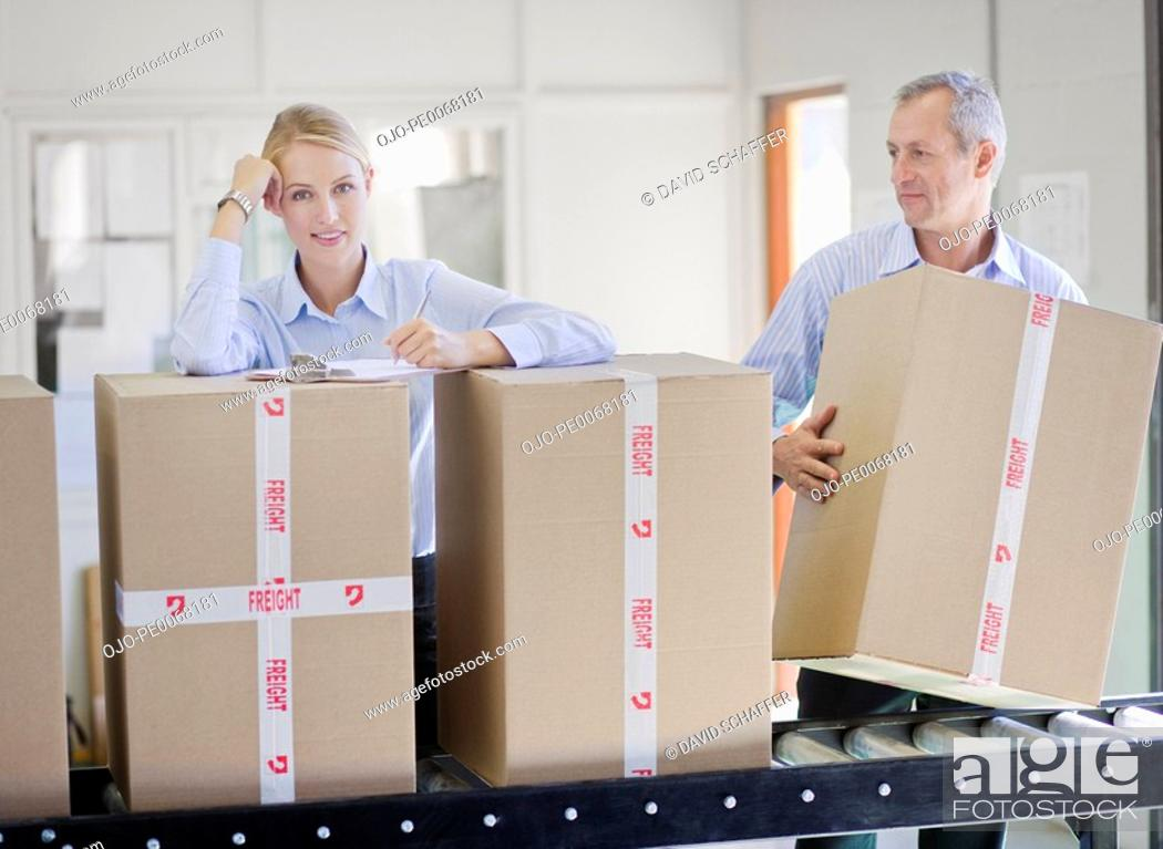 Stock Photo: Co-workers standing with boxes on conveyor belt.