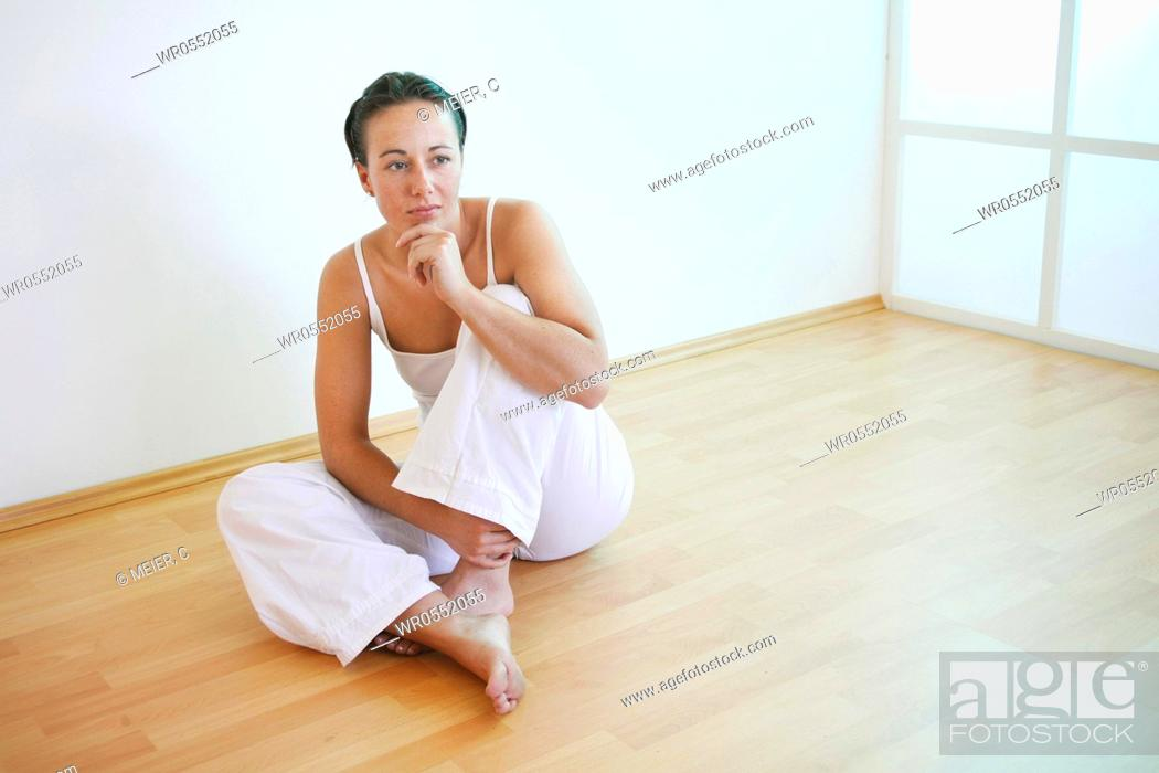 Imagen: Young woman sits with tucked up leg on the floor, her chin rests on her left hand.