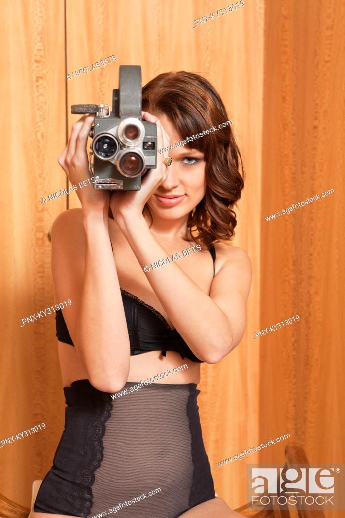 Stock Photo: Young woman in underwear using old-fashioned movie camera.