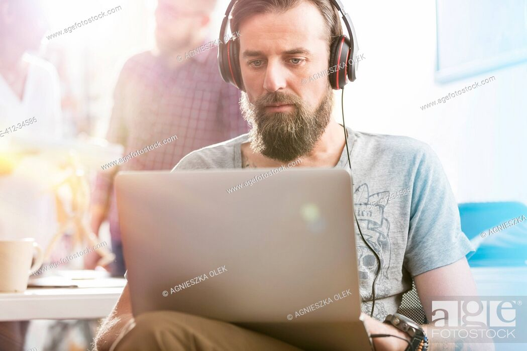 Stock Photo: Serious male design professional with headphones using laptop in office.