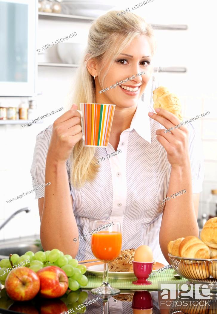 Stock Photo: woman having breakfast in kitchen.