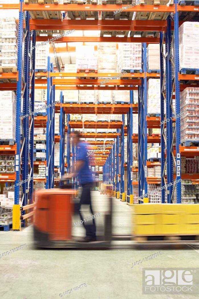 Stock Photo: Mid-adult Man Driving Pallet Jack Through Warehouse side view.