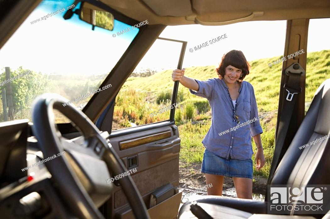 Stock Photo: Young woman by vehicle.