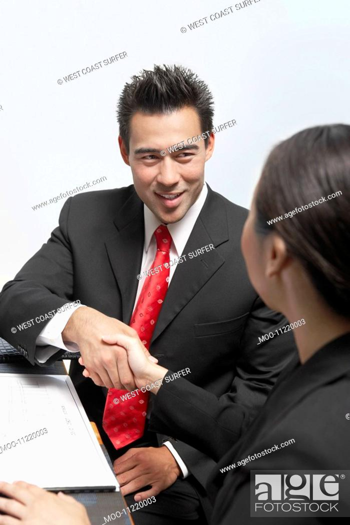 Stock Photo: Businessman and Businesswoman Shaking Hands at Table.