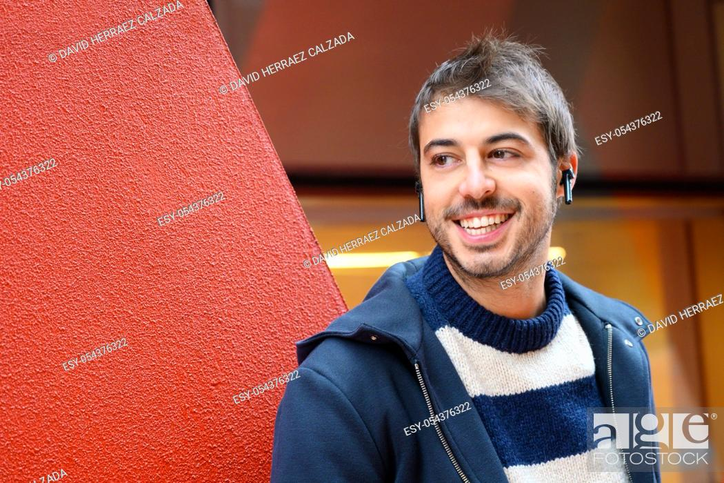 Stock Photo: Happy man listening to music with wireless earphones standing in the street near modern red office buildings .