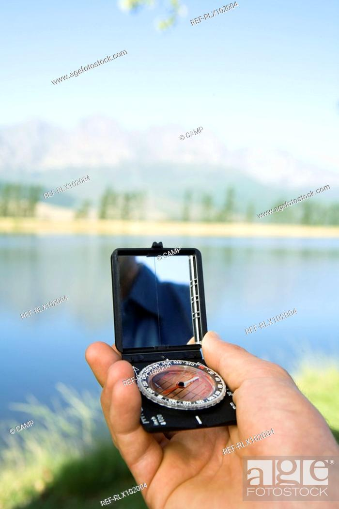 Stock Photo: Hand holding compass, outdoors, pointing at landscape, close-up.