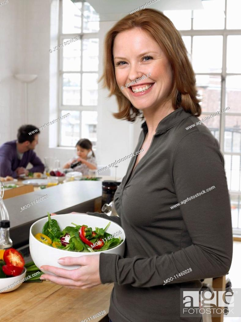 Stock Photo: Woman holding salad bowl in kitchen portrait.