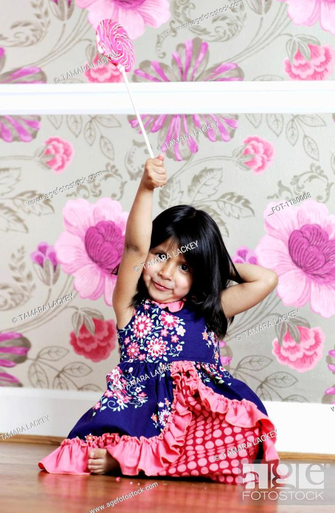 Stock Photo: A young girl holding a swirl lollipop aloft.
