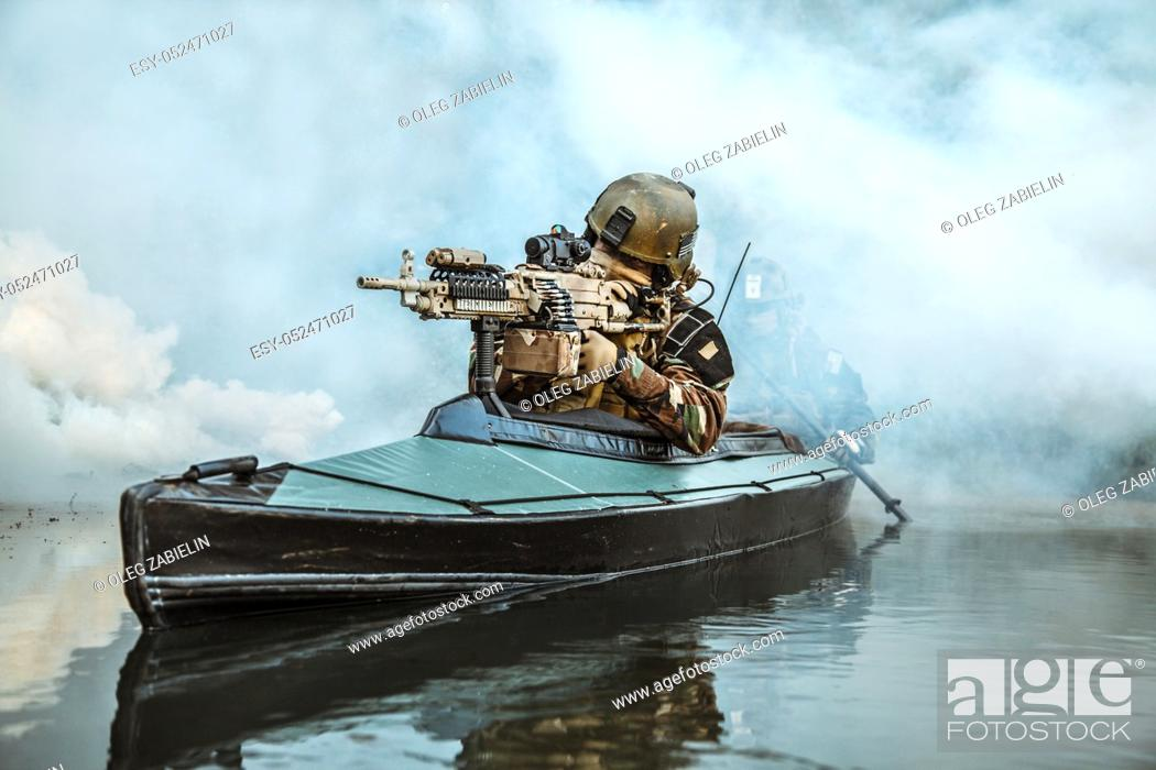 Imagen: Special forces marine operators in camouflage uniforms paddling army kayak through river fog. Diversionary mission, machine gunner ahead.