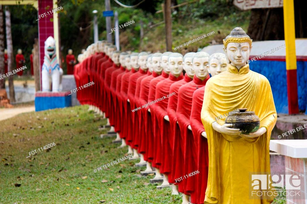 Stock Photo: A row of Buddhist monk statues in a procession behind a Buddha statue, Hpa-An, Burma.