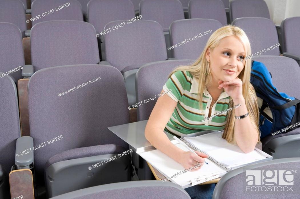 Stock Photo: Female student writing in lecture hall.