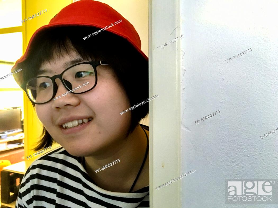 Stock Photo: Tilburg, Netherlands. Portrait of a young, Chinese woman watching.